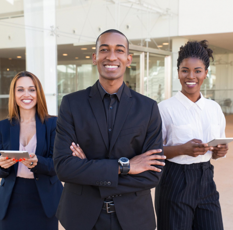 Happy cheerful business people posing in office hallway. Three multiethnic workers in formal suits standing for camera indoors and smiling. International cooperation concept